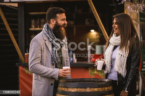Three quarter length of a couple of friends laughing and enjoying a hot beverage in a disposable cup next to a wooden barrel in a street market.