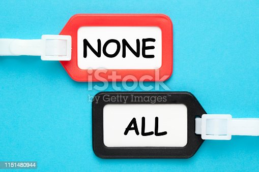 All or None words on luggage tags on blue background. Business concept.