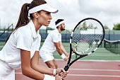 Young woman and man in white sportswear stand on the court with rackets in their hands fully concentrated on the game