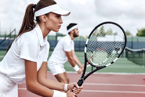 alles of niets. mooie vrouw en knappe man zijn concurrerend gericht op het spel - tennis stockfoto's en -beelden