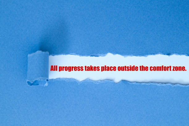 All progress takes place outside the comfort zone. All progress takes place outside the comfort zone written under torn paper. time zone stock pictures, royalty-free photos & images