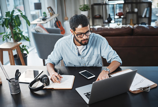 Shot of a young man using his laptop while working from home