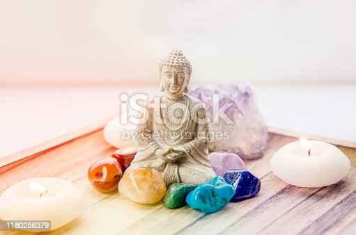 All seven red, orange, green, blue, purple chakra colors crystals stones around sitting Buddha figurine on natural wooden tray. Balance and calm energy flow in home concept.