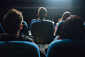 Rear view of the spectators in their seats watching movie at the cinema.
