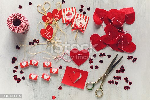 Directly above of a gray table with decorative elements like cards, cords and candies that someone is cutting for Valentine's Day.