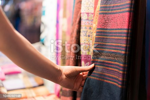 Close-up shot of a female hand choosing scarf at the street market.
