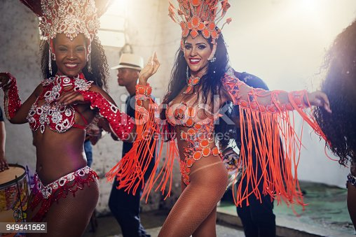 Portrait of two female dancers wearing vibrant costumes while dancing to music inside of a busy nightclub