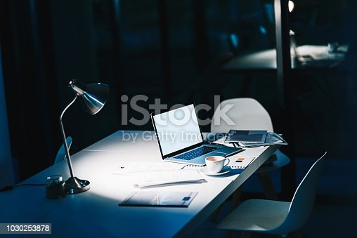 Shot of a laptop on a desk in a modern office at night with no people