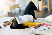 Shot of a young female student whose fallen asleep while studying at home