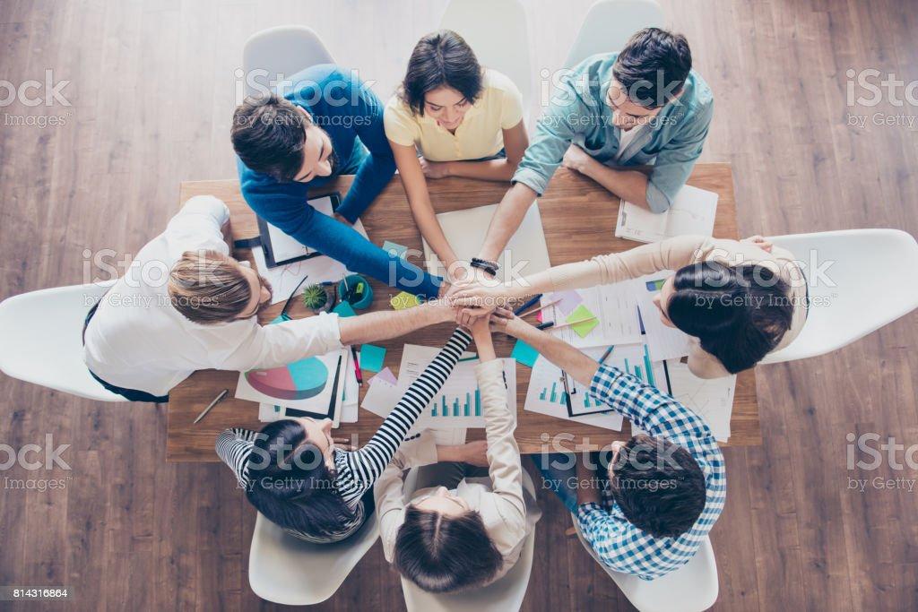 Todos juntos! Concepto de trabajo en equipo exitoso. Topview de empresarios poniendo sus manos encima de la otra en la agradable estación de trabajo ligero, ropa casual - foto de stock