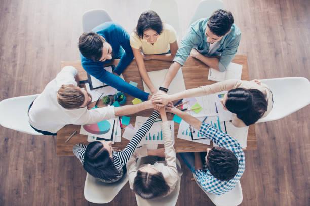 todos juntos! concepto de trabajo en equipo exitoso. topview de empresarios poniendo sus manos encima de la otra en la agradable estación de trabajo ligero, ropa casual - reunión evento social fotografías e imágenes de stock