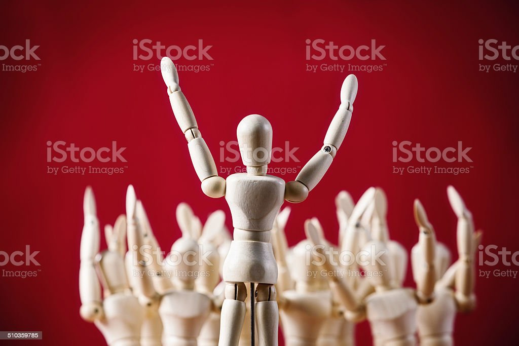 All together now! Puppet faces others, all with raised hands stock photo