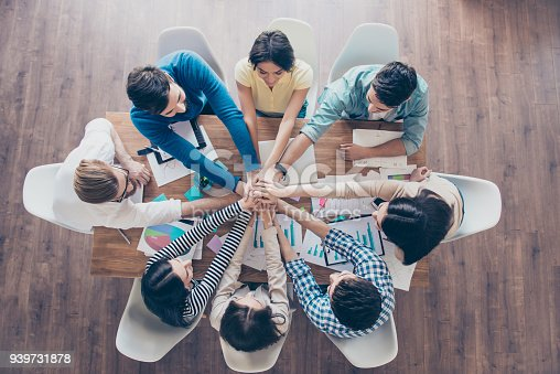 istock All together! Topview of businesspeople putting their hands on top of each other in nice light workstation, wearing casual clothes. Conception of successful teambuilding 939731878