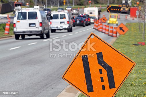 A standard move and merge  left sign with a digital flashing arrow and traffic cones advises all traffic to move into the left lane. Shot shallow dof with focus on foreground arrow sign.