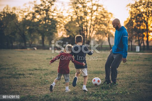 Father play soccer with sons. All happy and enjoy in nice spring sunset