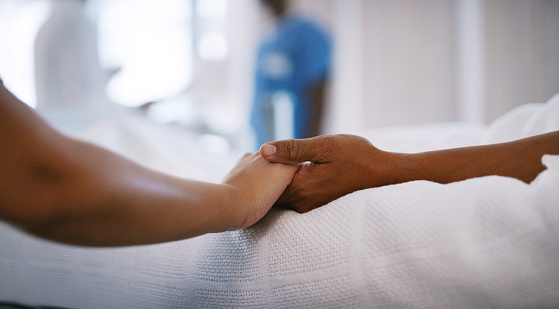 Closeup shot of an unrecognisable woman holding a patients hand in comfort in a hospital ward