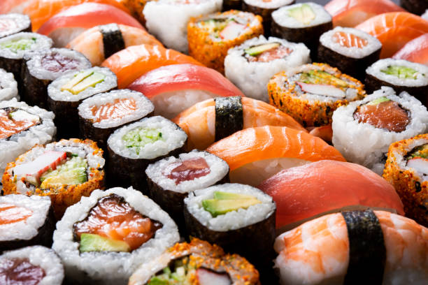 All you can eat sushi Overhead japanese sushi food. Maki ands rolls with tuna, salmon, shrimp, crab and avocado. Top view of assorted sushi, all you can eat menu. Rainbow sushi roll, uramaki, hosomaki and nigiri. asian food stock pictures, royalty-free photos & images