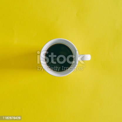 High angle shot of a cup of coffee on a yellow background