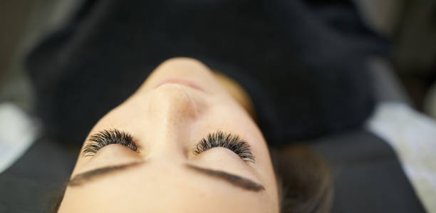 All you need is longer lashes! Cropped shot of a young woman getting eyelash extensions false eyelash stock pictures, royalty-free photos & images