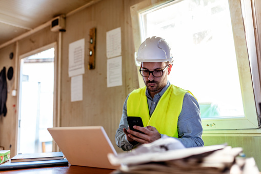 Serious Engineer looking at smartphone next to the laptop in office during the day. Engineer working with laptop on wood table in construction site, engineering technology concept.
