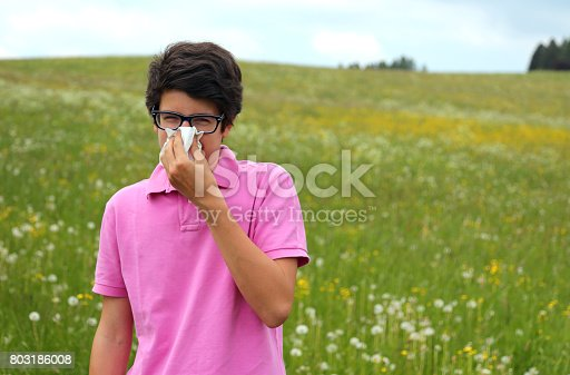 629307146istockphoto Allergic boy with glasses and pink t-shirt blows his nose 803186008