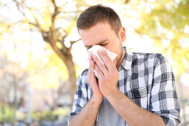 Allergic man sneezing covering nose with wipe stock photo