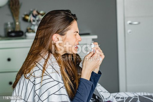 a young woman at home sneezes and suffering from allergies