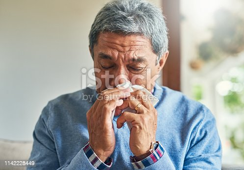 Shot of a sickly senior man blowing his nose with a tissue at home
