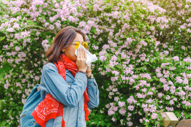 allergy concept. young asian woman sneezes and blowing her nose with a handkerchief and suffering in the spring among flowering and blooming trees. - primavera estação do ano imagens e fotografias de stock