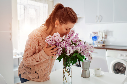 istock Allergy free. Happy woman smelling lilac in modern kitchen. Seasonal allergy concept. 958512286
