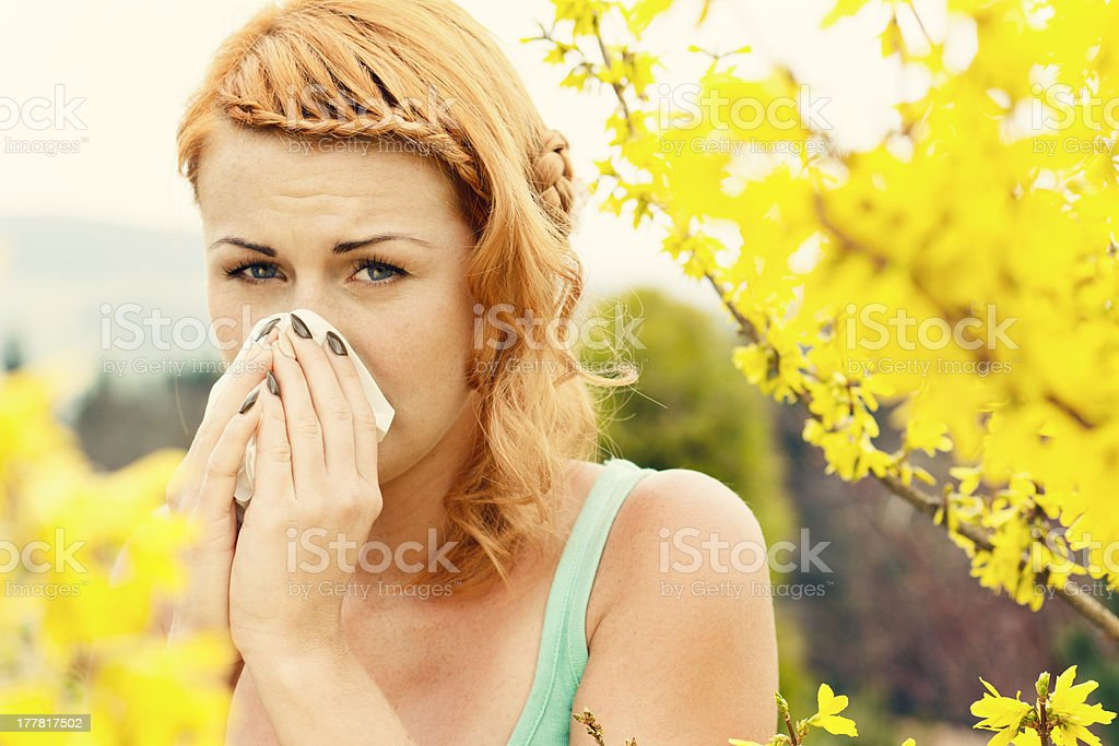 Young woman sneezing among flowers outdoors