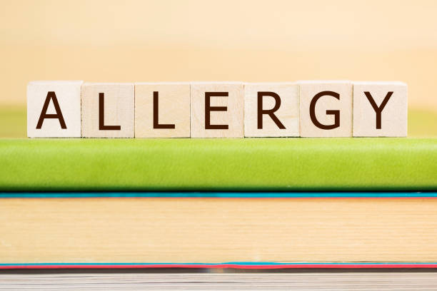 Allergy word built with letter cubes on green book stock photo