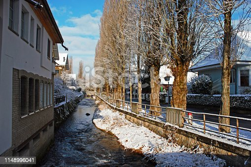 Alley next to the Lyssbach river, a small brook passing the city center of Lyss, Switzerland. Winter photo.