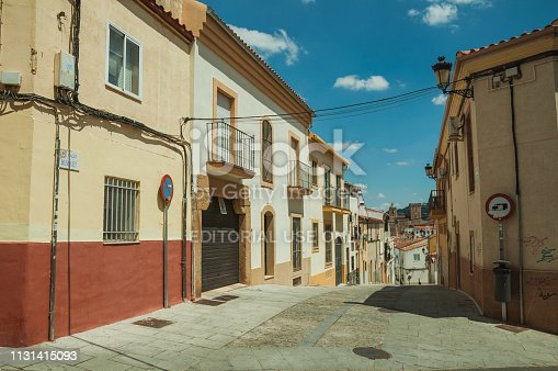 Caceres, Spain - July 03, 2018. Alley in slope with traffic signs and old buildings, in a sunny day at Caceres. A cute and charming town with a fully preserved medieval city center in western Spain.