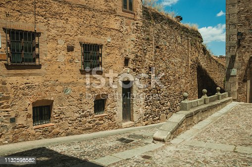 Alley with cobblestone pavement and old buildings, in a sunny day at Caceres. A cute and charming town with a fully preserved medieval city center in western Spain.