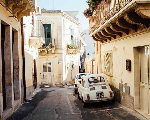 alley with old car 500, italy - noto sicilië stockfoto's en -beelden