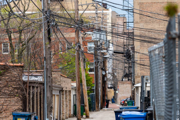 Allee mit Stromleitungen und Kettenglitzaun – Foto