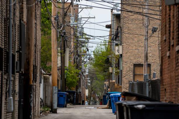 Alley mit Stromleitungen, Mülleimer und Schmutz in Pfützen – Foto