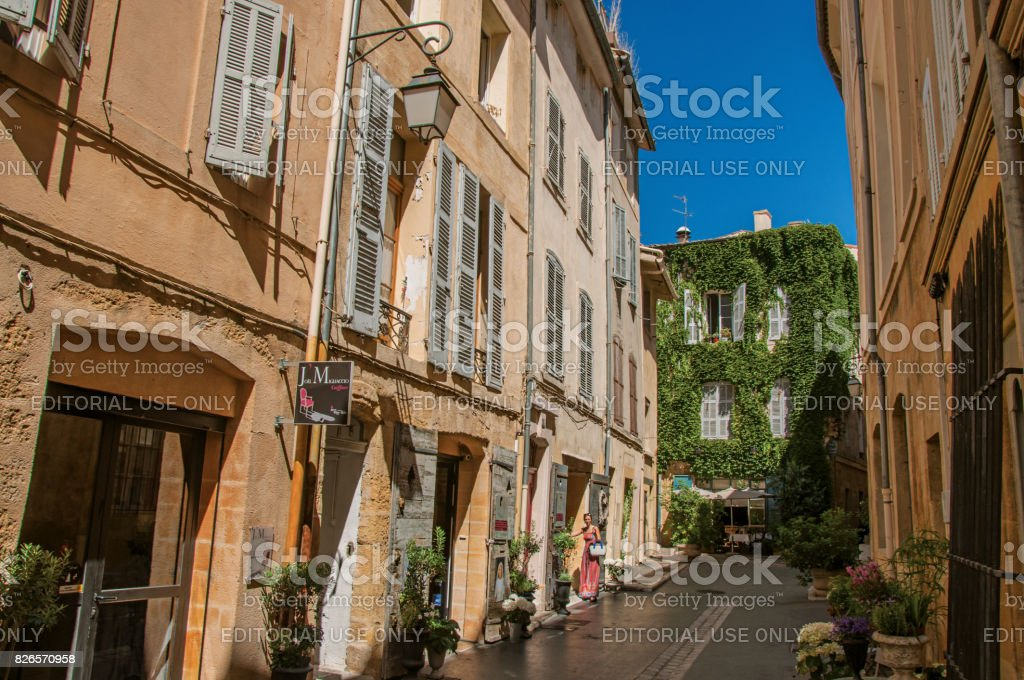 Alleyway with woman entering the house in Aix-en-Provence. stock photo