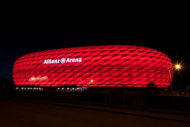 allianz arena, das fußballstadion des fc bayern, rot bei nacht beleuchtet - bayern fußball heute stock-fotos und bilder