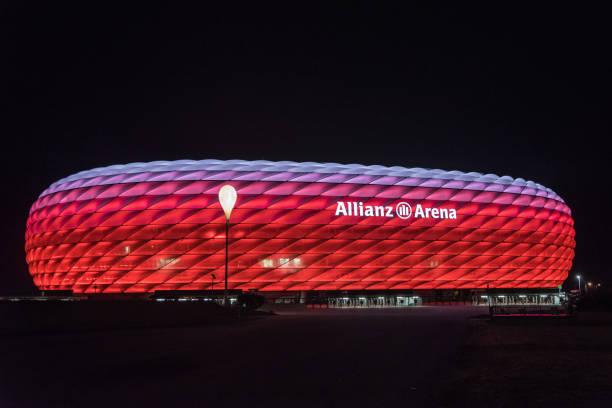 allianz arena, dem fußballstadion des fc bayern, in rot mit weißen oben nachts beleuchtet - bayern fußball heute stock-fotos und bilder