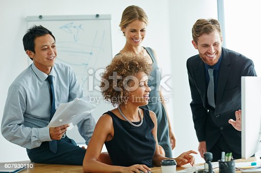 Shot of a group of businesspeople discussing something on a computer