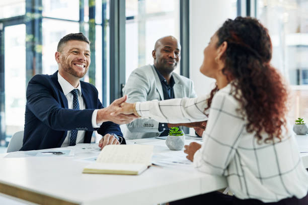 Allow me to be the first to welcome you to the team Shot of businesspeople shaking hands in an office job interview stock pictures, royalty-free photos & images