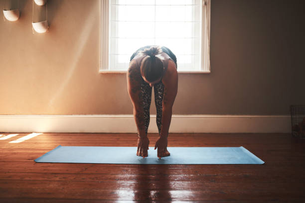 Allow yourself to be calm as you transform Shot of a young woman exercising at home touching toes stock pictures, royalty-free photos & images