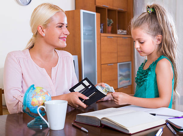 Allowance of pocket money Allowance of pocket money:  little girl and smiling mother with purse allowance stock pictures, royalty-free photos & images