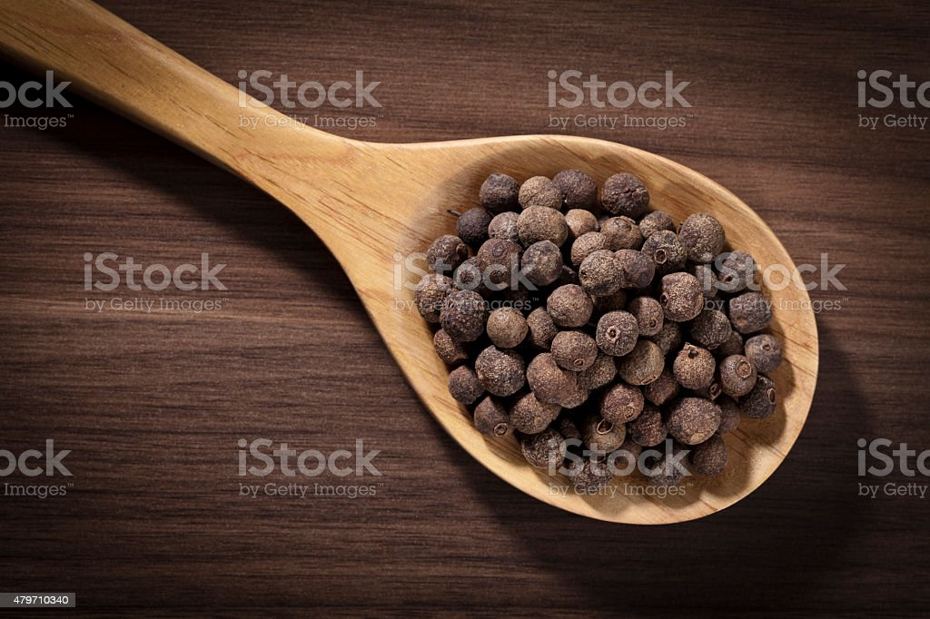 Allspice in a wooden spoon shot directly above stock photo