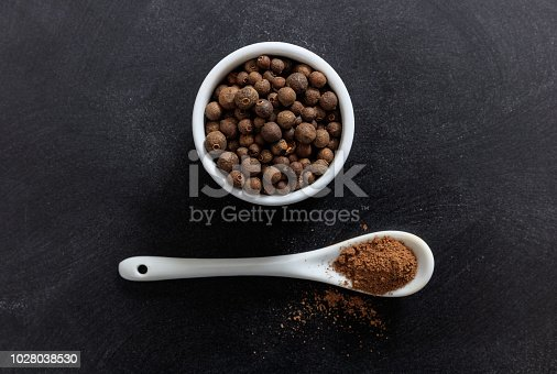 Allspice in porcelain bowl and spoon, black background