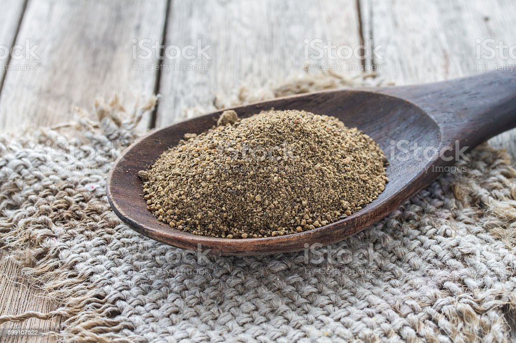 allspice in wooden ladle on wood background, allspice on sack, stock photo