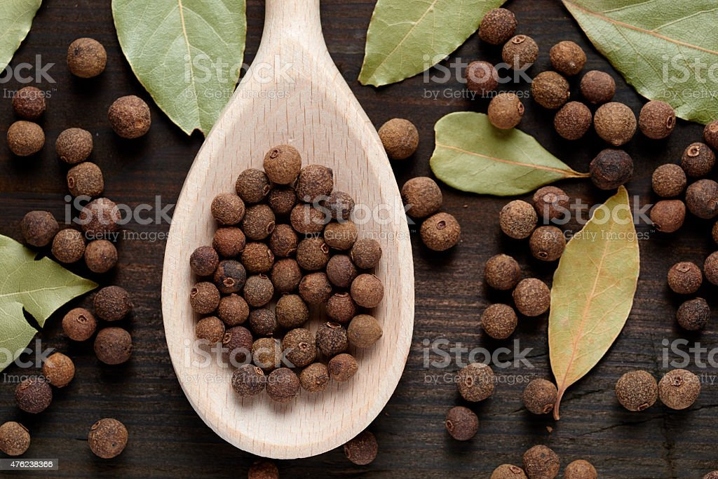 allspice on a wooden spoon surrounded by a bay leaf stock photo