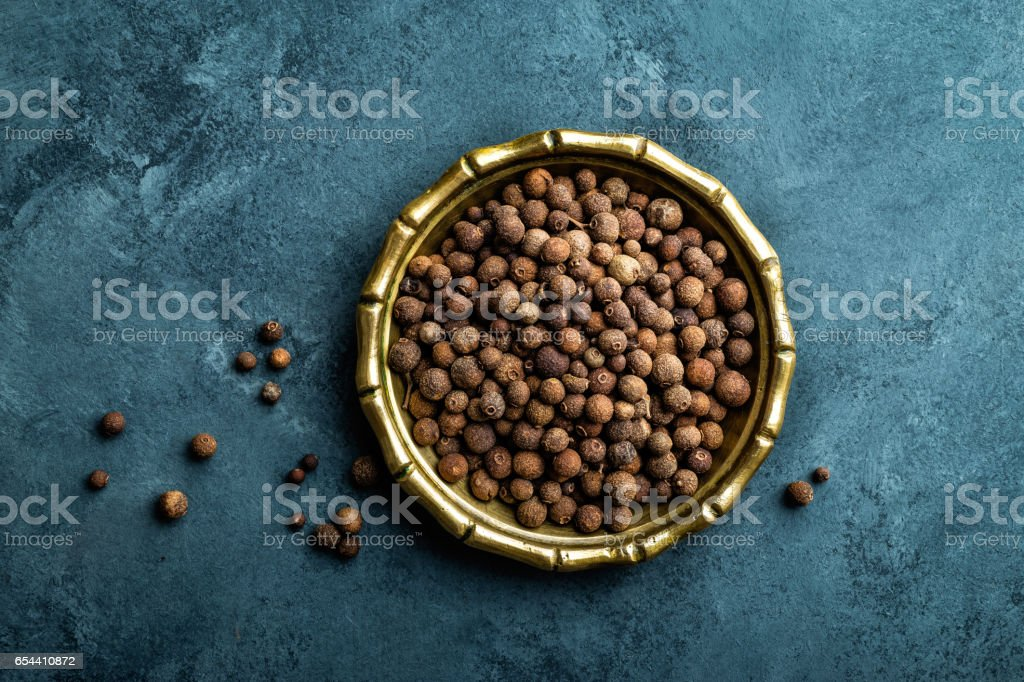 Allspice pepper, peppercorns on dark culinary background, top view, copy space stock photo